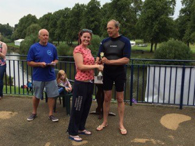 The High Sheriff, in wetsuit,  presents Caroline Saxon with the prize for being the fastest woman without a wetsuit.